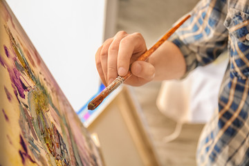 Male artist painting in workshop, closeup