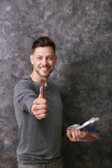 Male artist holding paintbrush on grey background