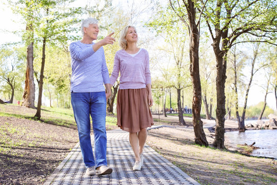 Mature couple walking in park on spring day