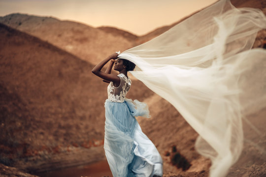 Black bride stands and holds waving bridal veil in her hands on background of beautiful landscape.