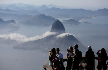 Tourists are seen with the Sugarloaf Mountain in the background in Rio de Janeiro