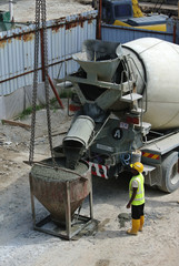 Concrete mixer lorry pouring wet concrete into concrete bucket at the construction site.