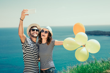 Smiling couple wearing sunglasses with balloons make selfie photo over sea background