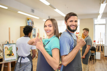Students showing thumb-up gesture in art school