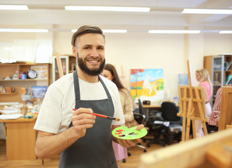 Male art student painting in workshop