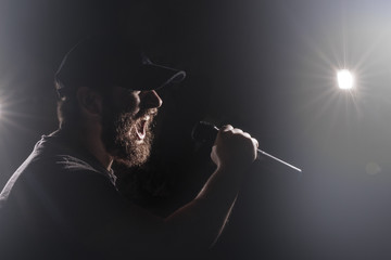 bearded man in a cap with a microphone in his hand sings with a drive, concept singer on stage, toned image