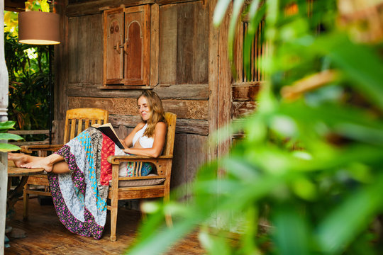 Attractive girl sit on open-air veranda of wooden bungalow with tropical garden view, read romance in paper book. Young woman relaxing in luxury villa on family summer vacation. Countryside lifestyle.