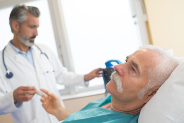 doctor with sick old man lying in hospital bed