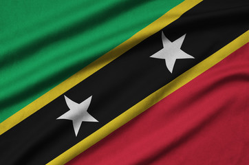 Saint Kitts and Nevis flag  is depicted on a sports cloth fabric with many folds. Sport team banner