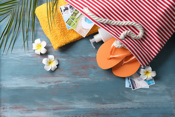 Bag with beach accessories on wooden background