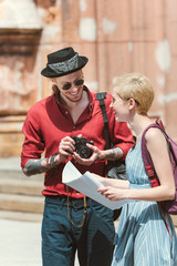 beautiful couple of tourists with photo camera and map