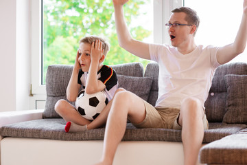 Young father and his son watching world soccer championship with ball on