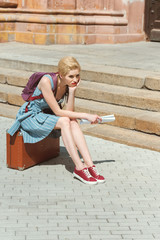 beautiful girl with backpack and newspaper sitting on retro travel bag