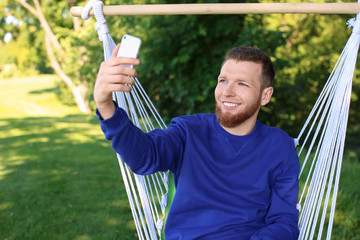 Young man taking selfie with mobile phone in hammock outdoors