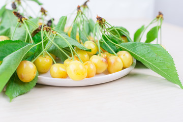 White-yellow ripe sweet cherry with leaves on a white plate on a wooden background. Close-up, minimal summer concept.