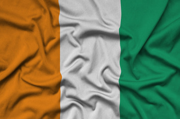 Ivory Coast flag  is depicted on a sports cloth fabric with many folds. Sport team banner