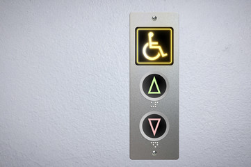 Elevator buttons panel with an amber glowing light button for handicap and Braille code for the visually impaired.