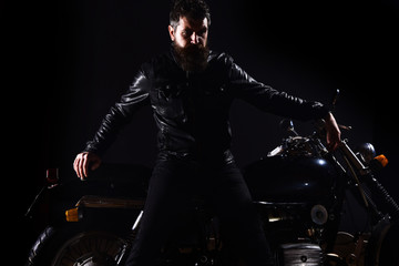Macho, brutal biker in leather jacket stand near motorcycle at night time, copy space. Man with beard, biker in leather jacket lean on motor bike in darkness, black background. Biker culture concept.