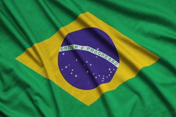 Brazil flag  is depicted on a sports cloth fabric with many folds. Sport team banner