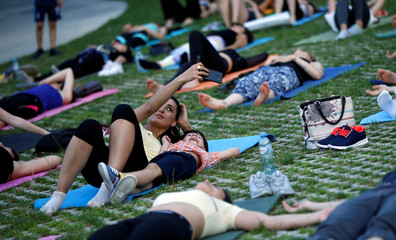 A woman takes a selfie during a yoga class on International Yoga Day in Tbilisi
