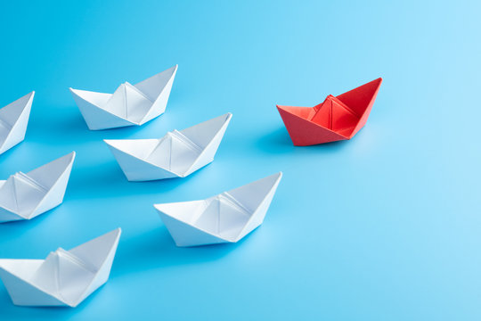 Leadership concept. Red leader paper ship leading among white on blue background.