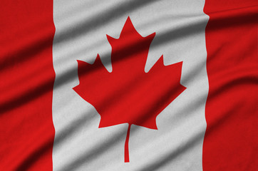 Canada flag  is depicted on a sports cloth fabric with many folds. Sport team banner