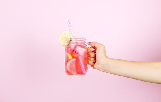 Young woman hands holding freshly squeezed strawberry lemonade of citrus fruits. Female with mason jar full of cold cocktail, lemon, orange, lime & mint leaves. Pink background, copy space, close up.