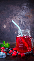 Drink Summer from Mix Berries Decorated with Green Mint. Compote in in a glass jar with a straw. Old dark Background. Superfoods and healthy lifestyle or detox diet food concept.