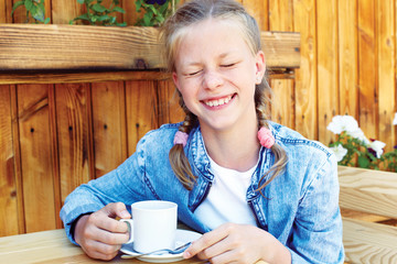 Girl laughing fun while sitting at a coffee in a street cafe.