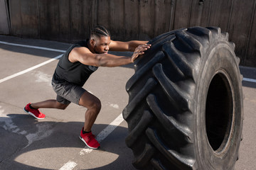 high angle view of athletic african american man exercising with tyre on street
