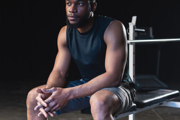 cropped shot of young african american sportsman with talcum powder on hands sitting and looking away
