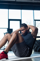focused young african american sportsman doing abs in gym