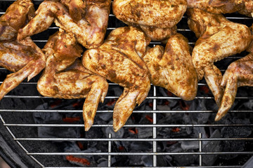 Spicy cooking chicken wings grilling on a summer barbecue