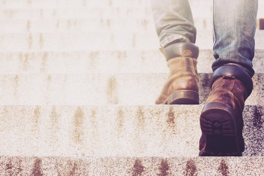 Close up legs of young hipster man One person walking stepping going up the stairs in modern city,  go up, success, grow up. with filter Tones retro vintage warm effect.