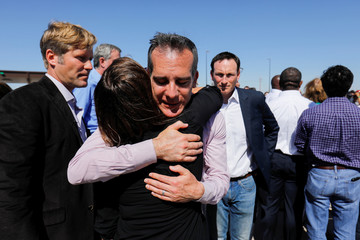 Los Angeles mayor Eric Garcetti hugs Elizabeth J. Kistin Keller the wife of Albuquerque mayor Tim Keller outside the children's tent encampment following a group of U.S. mayors press conference Tornillo
