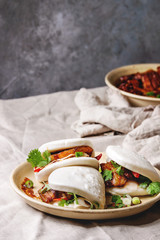 Asian sandwich steamed gua bao buns with pork belly, greens and vegetables served in ceramic plate on table with linen tablecloth. Asian style fast food dinner.