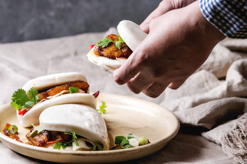 Man's hands hold asian sandwich steamed gua bao buns with pork belly, greens and vegetables served in ceramic plate on table with linen tablecloth. Asian style fast food dinner.