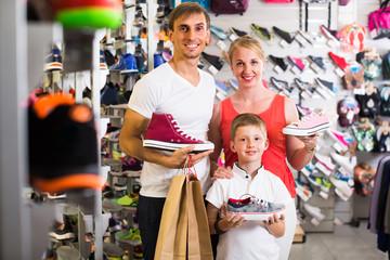 Family choosing shoes in sport shop.