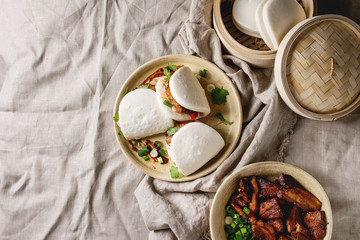 Asian sandwich steamed gua bao buns with pork belly, greens and vegetables served in ceramic plate over linen tablecloth. Asian style fast food dinner. Flat lay, space