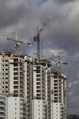 Construction work of high-rise residential buildings.Active construction of the housing complex, with the working cranes .