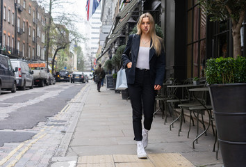Teenage girl walking down a street in London after shopping