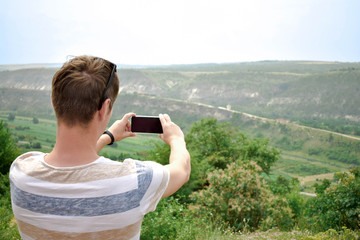 Young man making mobile photo of landscape