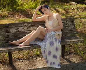 Woman in Long Skirt and Crochet Vest on Park Bench