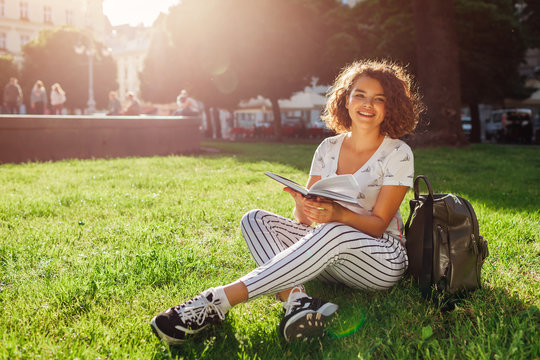 Beautiful college girl reading a book in campus park. Happy woman student learning outdoors