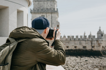 A professional photographer or a young male tourist photographes the sights in Lisbon in Portugal