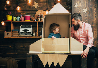 Rocket launch concept. Kid happy sit in hand made rocket. Child cute boy play cosmonaut or astronaut. happy family play with rocket made out of cardboard box