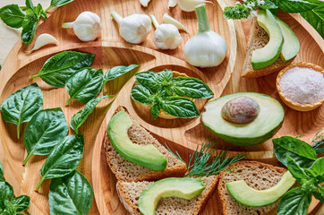 Avocado toasts on the wooden plate with  garlic, basil, dill and salt. Vegan avocado sandwiches decorated with basil leaves on the wooden background. Healthy green diet concept. Close up view