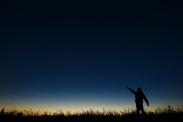 Astronomer points his hand at night the starry sky on a background of a twilight horizon.