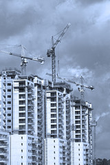 Construction work of high-rise residential buildings.Active construction of the housing complex, with the working cranes .Blue Toned