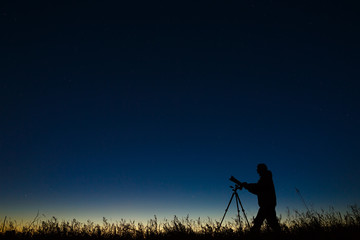 The astronomer photographs the night starry sky on a digital camera using a tripod.
